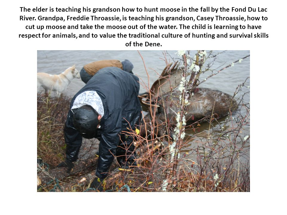 The elder is teaching his grandson how to hunt moose in the fall by the Fond Du Lac River.
