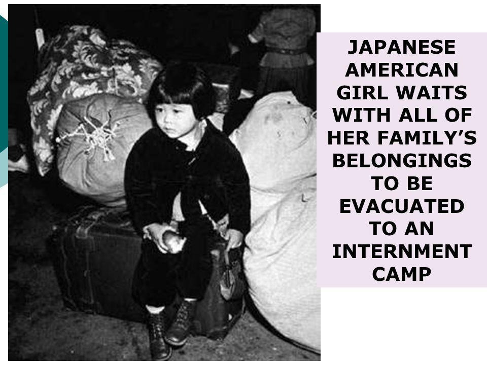 JAPANESE AMERICAN GIRL WAITS WITH ALL OF HER FAMILY'S BELONGINGS TO BE EVACUATED TO AN INTERNMENT CAMP
