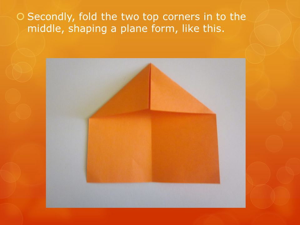 Secondly, fold the two top corners in to the middle, shaping a plane form, like this.
