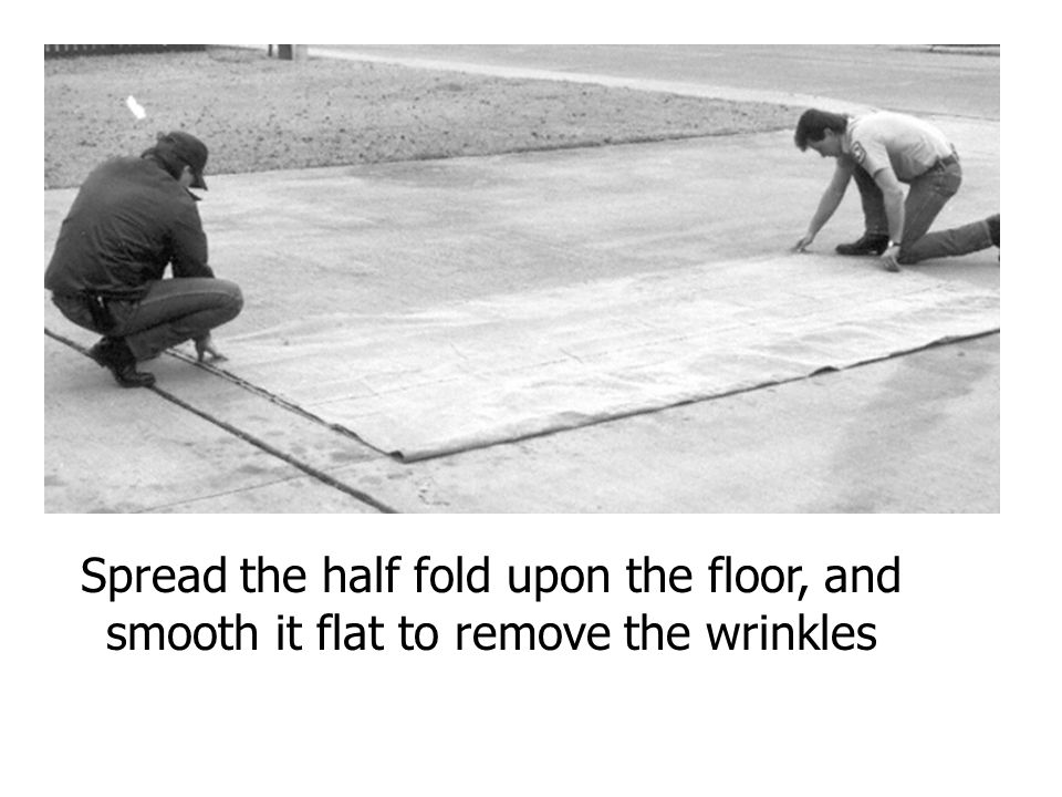 Spread the half fold upon the floor, and smooth it flat to remove the wrinkles