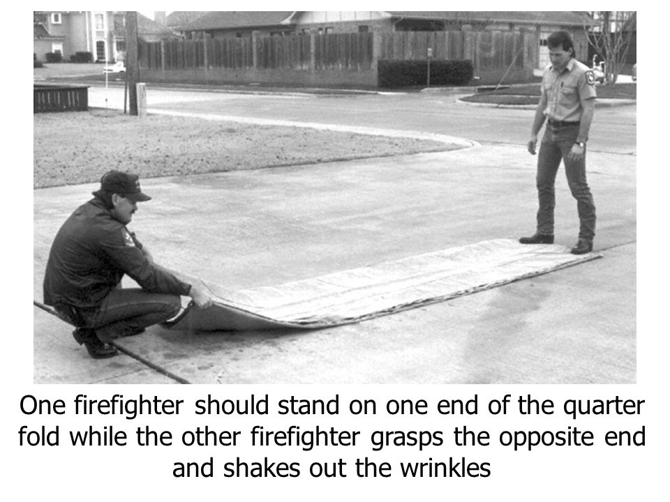 One firefighter should stand on one end of the quarter fold while the other firefighter grasps the opposite end and shakes out the wrinkles