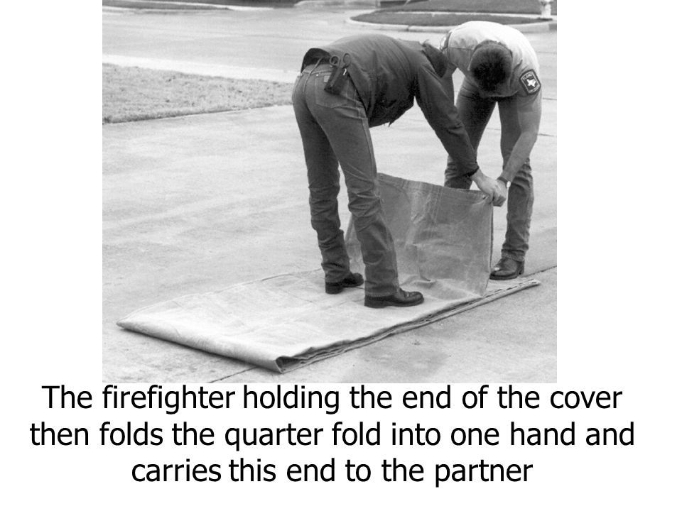The firefighter holding the end of the cover then folds the quarter fold into one hand and carries this end to the partner