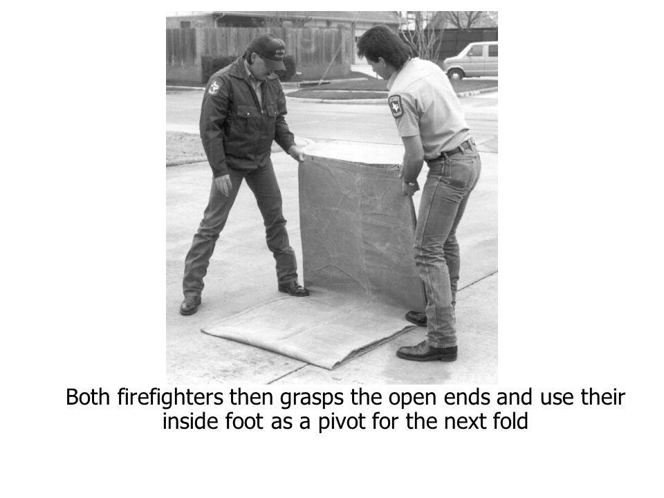 Both firefighters then grasps the open ends and use their inside foot as a pivot for the next fold