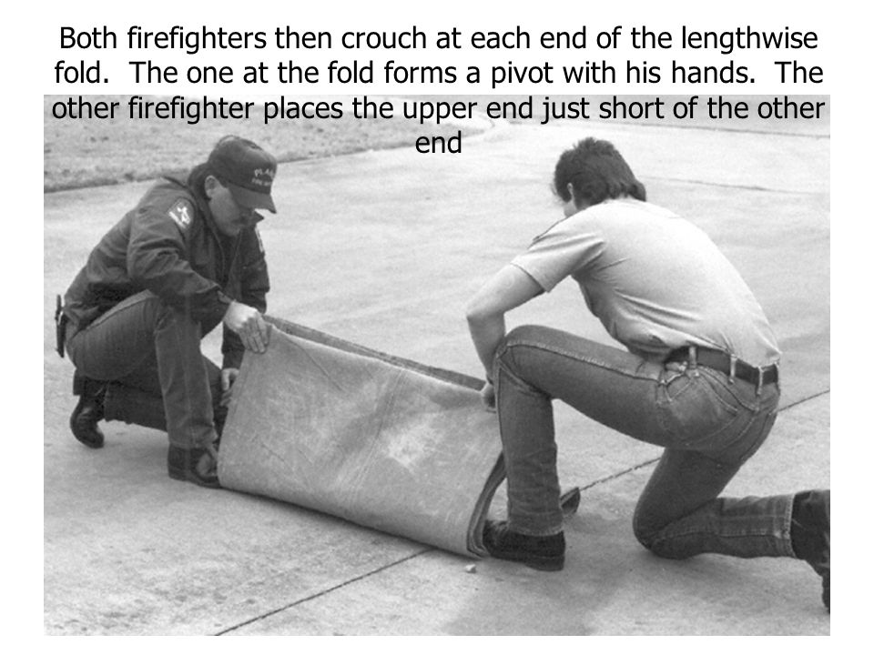 Both firefighters then crouch at each end of the lengthwise fold