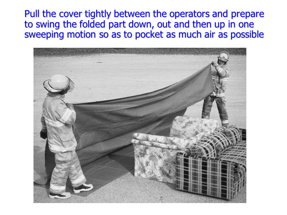 Pull the cover tightly between the operators and prepare to swing the folded part down, out and then up in one sweeping motion so as to pocket as much air as possible