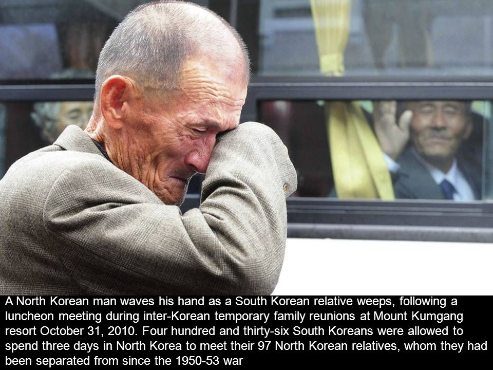 A North Korean man waves his hand as a South Korean relative weeps, following a luncheon meeting during inter-Korean temporary family reunions at Mount Kumgang resort October 31, 2010.