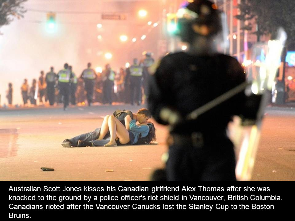 Australian Scott Jones kisses his Canadian girlfriend Alex Thomas after she was knocked to the ground by a police officer s riot shield in Vancouver, British Columbia.