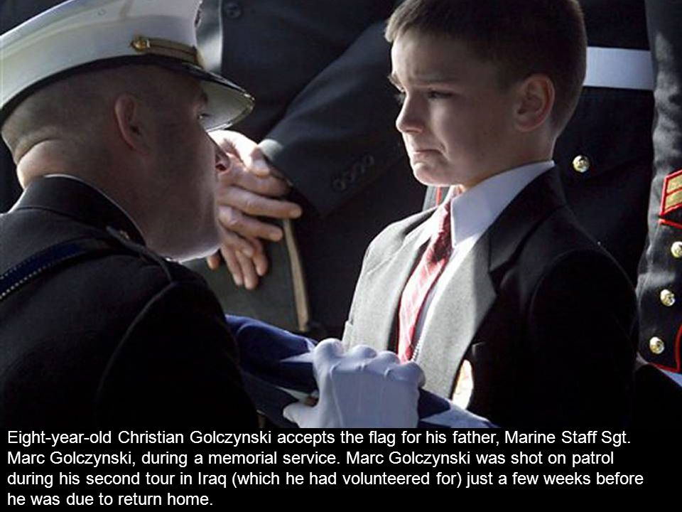 Eight-year-old Christian Golczynski accepts the flag for his father, Marine Staff Sgt.