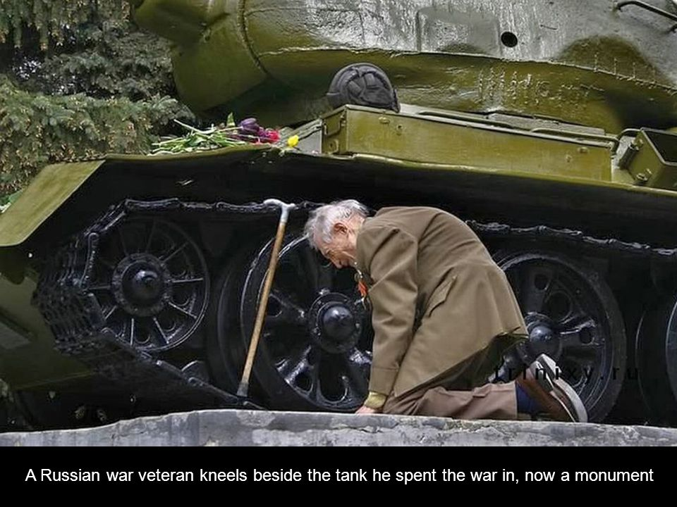A Russian war veteran kneels beside the tank he spent the war in, now a monument