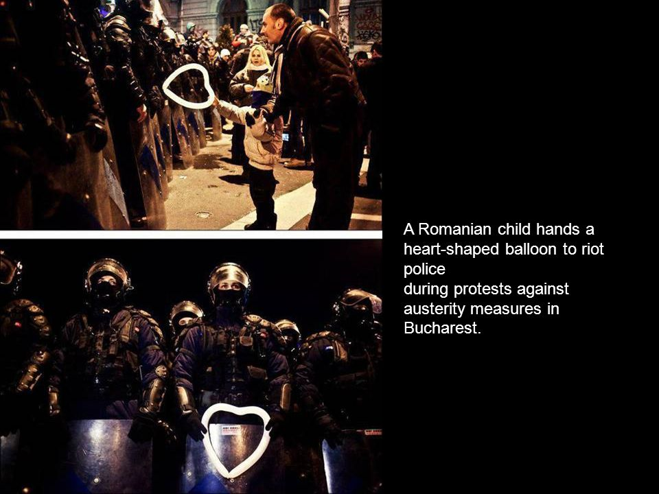 A Romanian child hands a heart-shaped balloon to riot police
