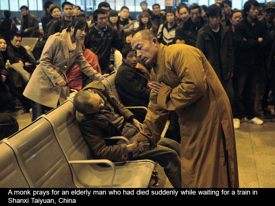 A monk prays for an elderly man who had died suddenly while waiting for a train in Shanxi Taiyuan, China