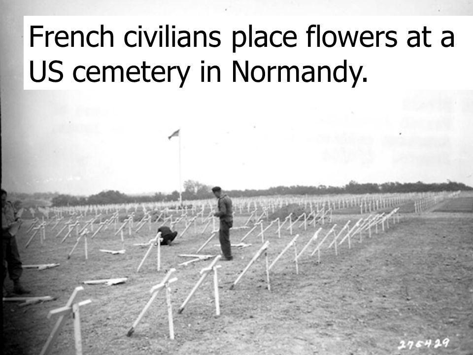 French civilians place flowers at a US cemetery in Normandy.