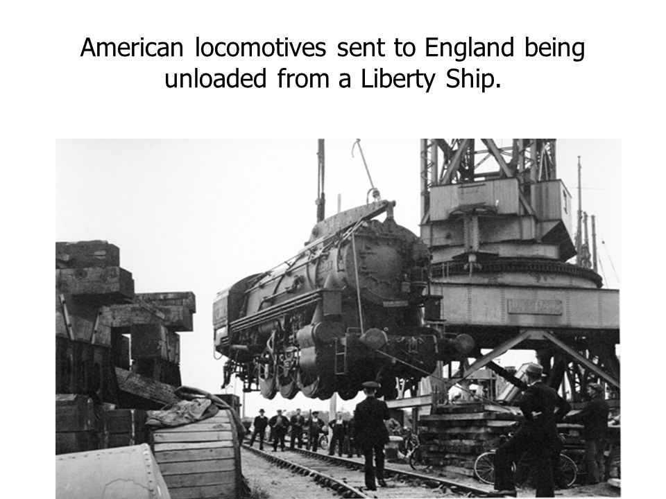 American locomotives sent to England being unloaded from a Liberty Ship.