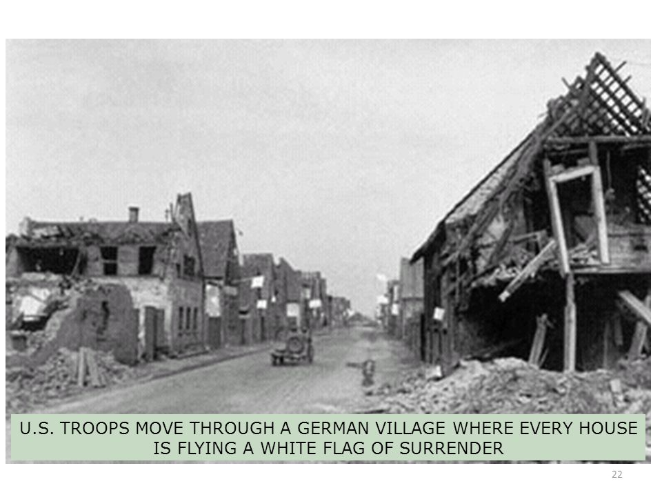 U.S. TROOPS MOVE THROUGH A GERMAN VILLAGE WHERE EVERY HOUSE IS FLYING A WHITE FLAG OF SURRENDER