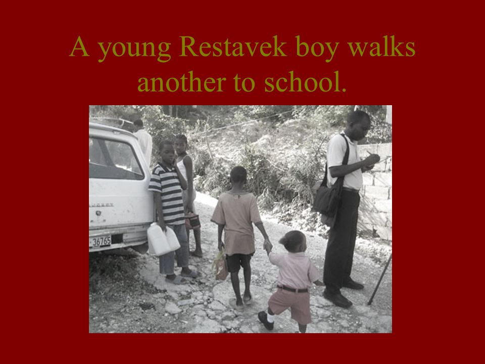 A young Restavek boy walks another to school.