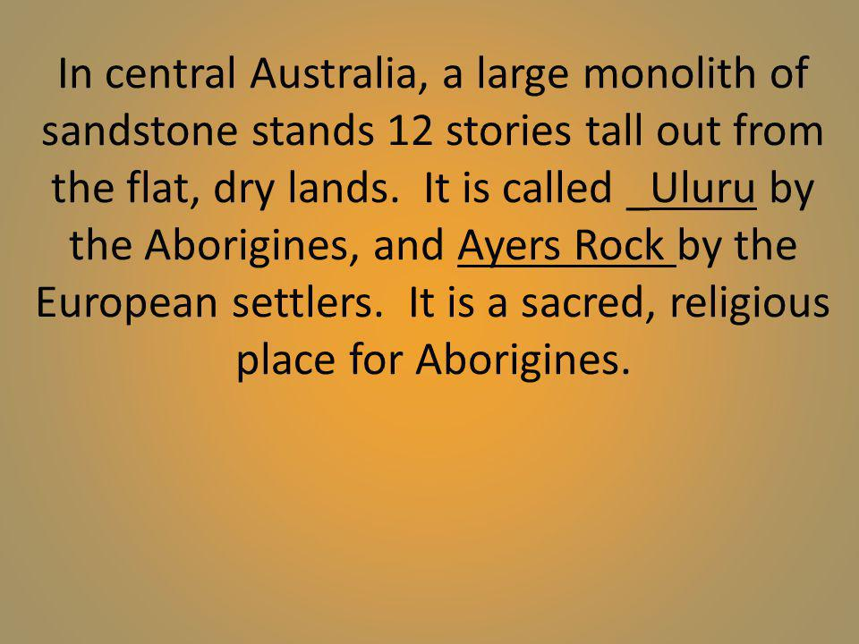 In central Australia, a large monolith of sandstone stands 12 stories tall out from the flat, dry lands.