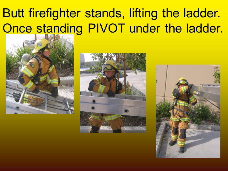 Butt firefighter stands, lifting the ladder.