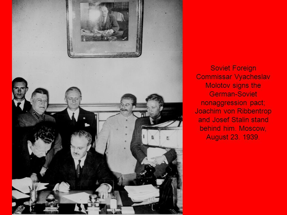Soviet Foreign Commissar Vyacheslav Molotov signs the German-Soviet nonaggression pact; Joachim von Ribbentrop and Josef Stalin stand behind him.