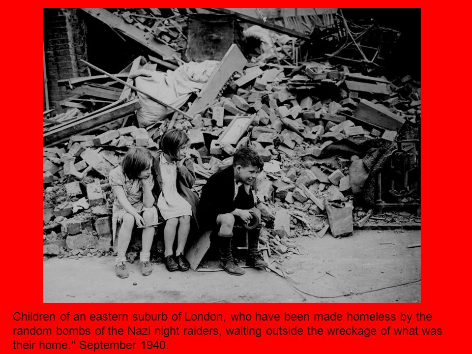 Children of an eastern suburb of London, who have been made homeless by the random bombs of the Nazi night raiders, waiting outside the wreckage of what was their home. September 1940.