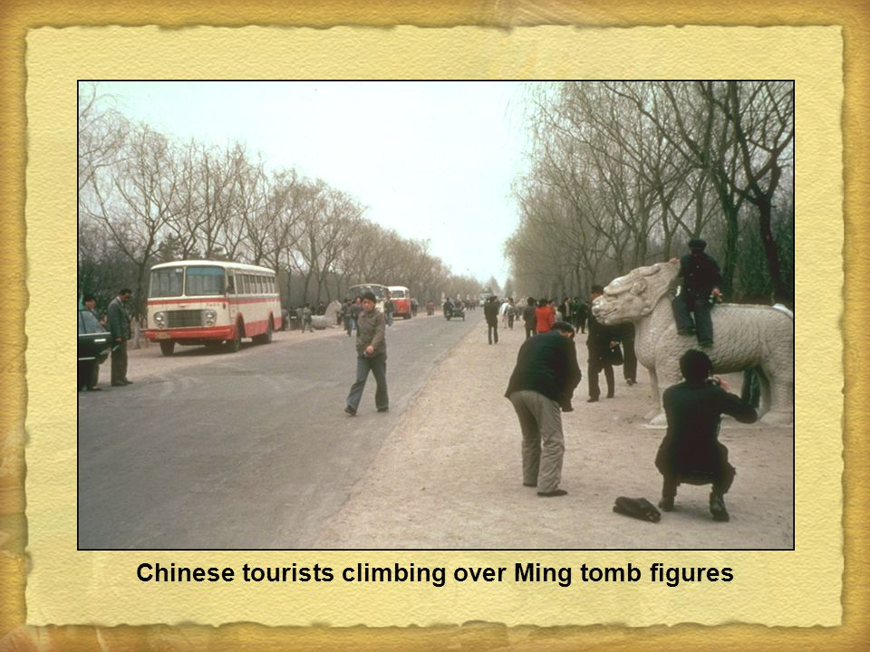 Chinese tourists climbing over Ming tomb figures
