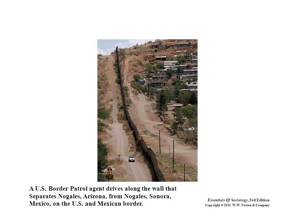 A U.S. Border Patrol agent drives along the wall that