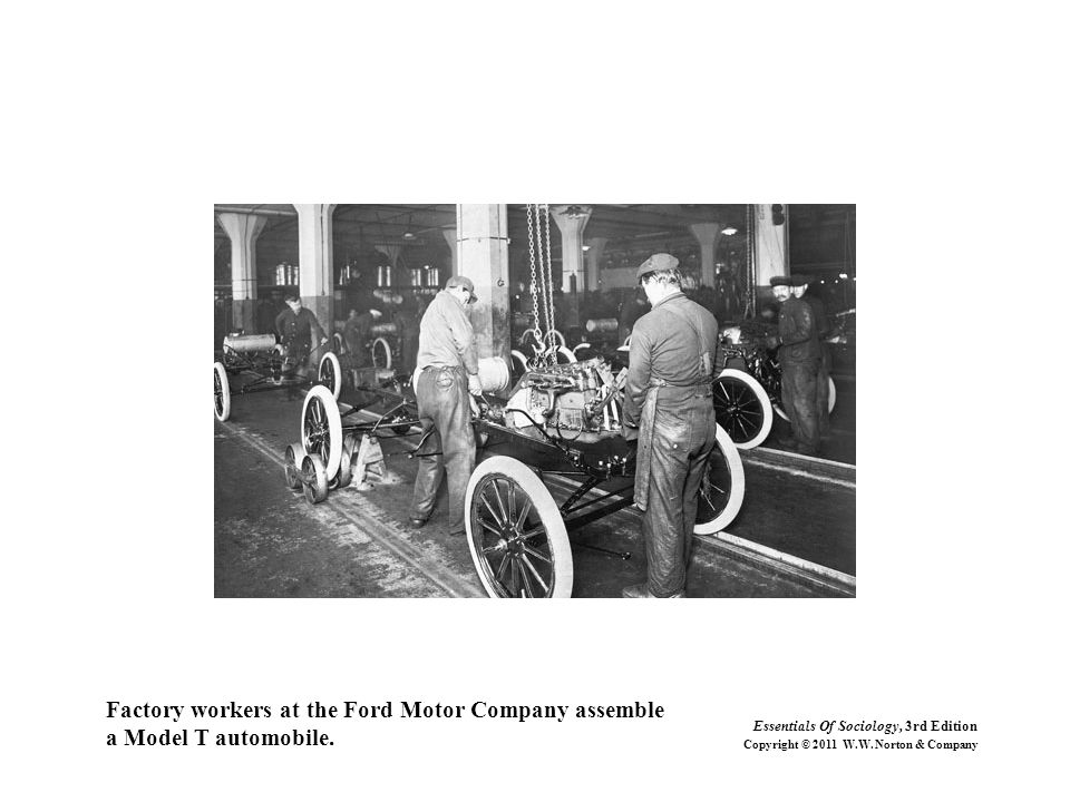 Factory workers at the Ford Motor Company assemble