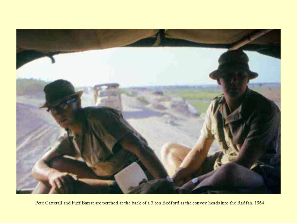 Pete Catterall and Fuff Barrat are perched at the back of a 3 ton Bedford as the convoy heads into the Radfan.