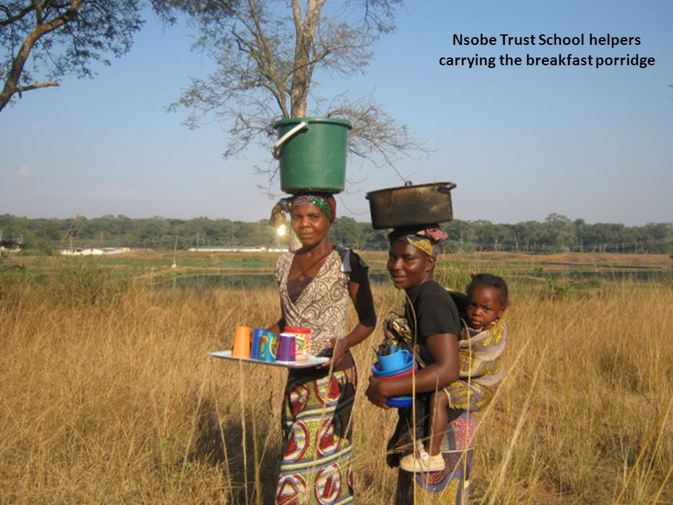 Nsobe Trust School helpers carrying the breakfast porridge