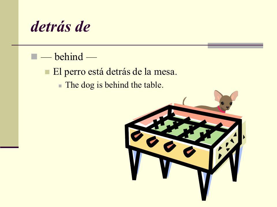 detrás de — behind — El perro está detrás de la mesa.