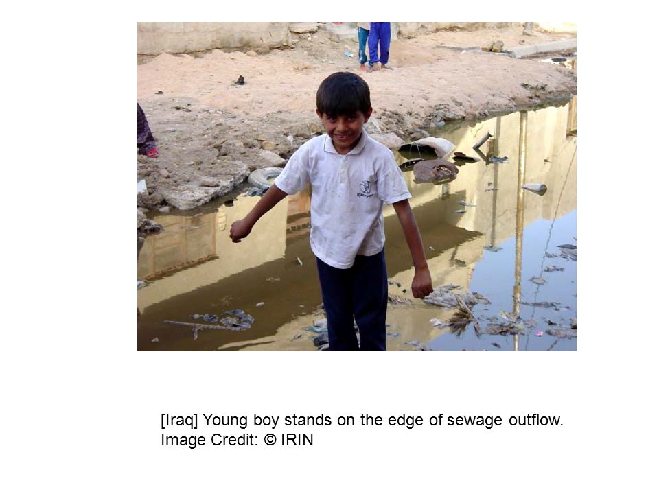 [Iraq] Young boy stands on the edge of sewage outflow