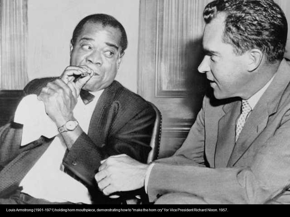 Louis Armstrong (1901-1971) holding horn mouthpiece, demonstrating how to make the horn cry for Vice President Richard Nixon.