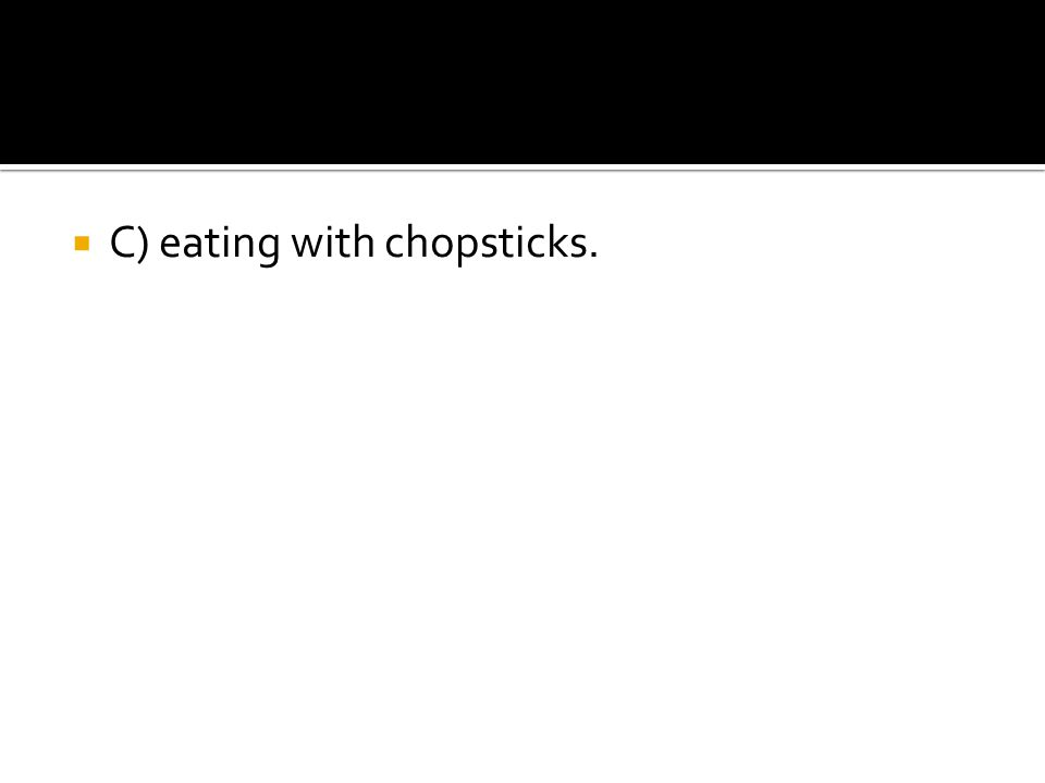 C) eating with chopsticks.