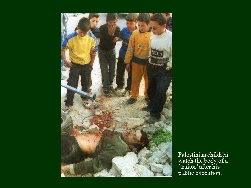 Palestinian children watch the body of a 'traitor' after his public execution.