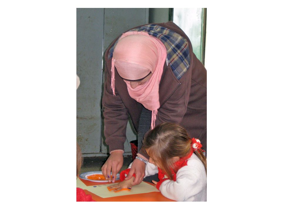 This teacher was directly assisting this child in making a paint handprint on a piece of paper. She is employing the hand-over-hand technique, in which she guided the child's hand onto the paint plate and then onto the paper and pressed the child's fingers down with her own.