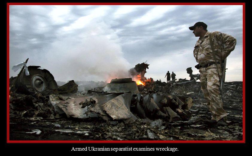 Armed Ukranian separatist examines wreckage.