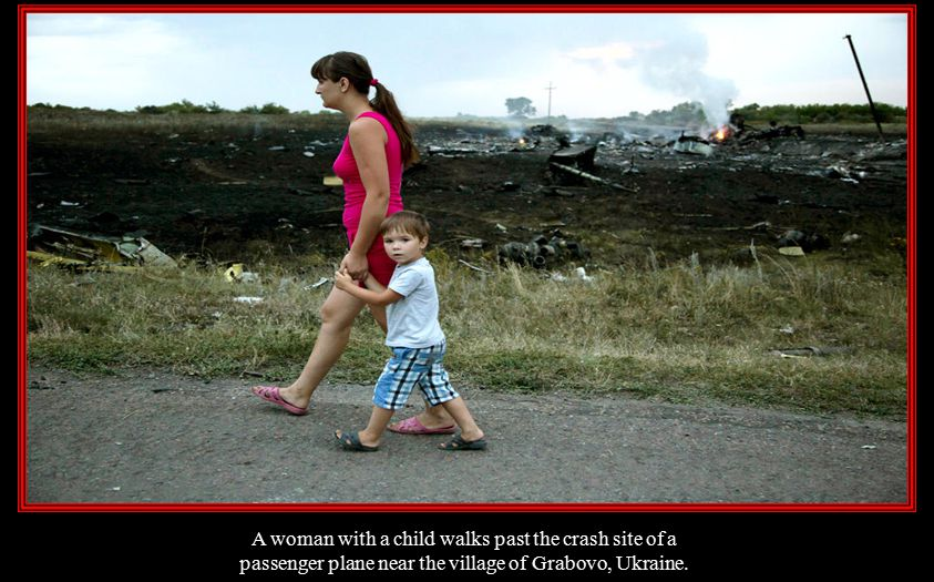 A woman with a child walks past the crash site of a