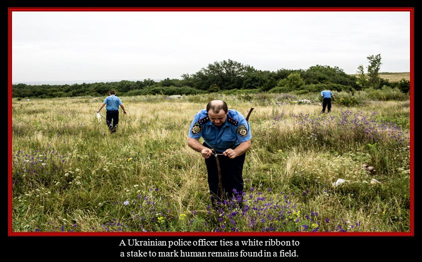 A Ukrainian police officer ties a white ribbon to