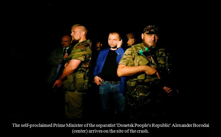 The self-proclaimed Prime Minister of the separatist Donetsk People s Republic Alexander Borodai (center) arrives on the site of the crash.