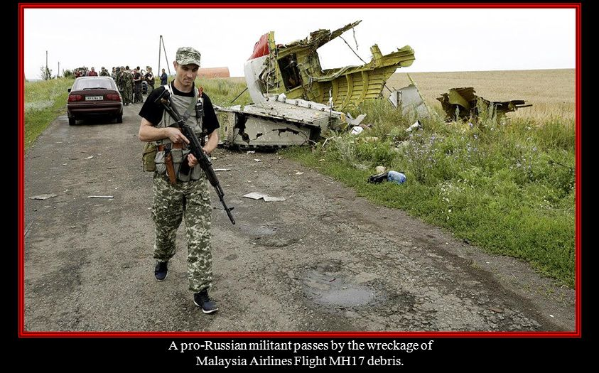A pro-Russian militant passes by the wreckage of