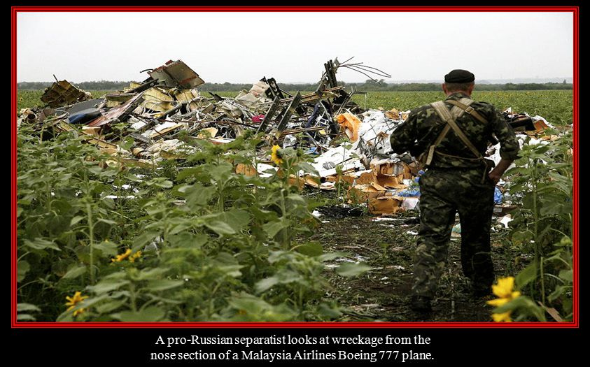 A pro-Russian separatist looks at wreckage from the
