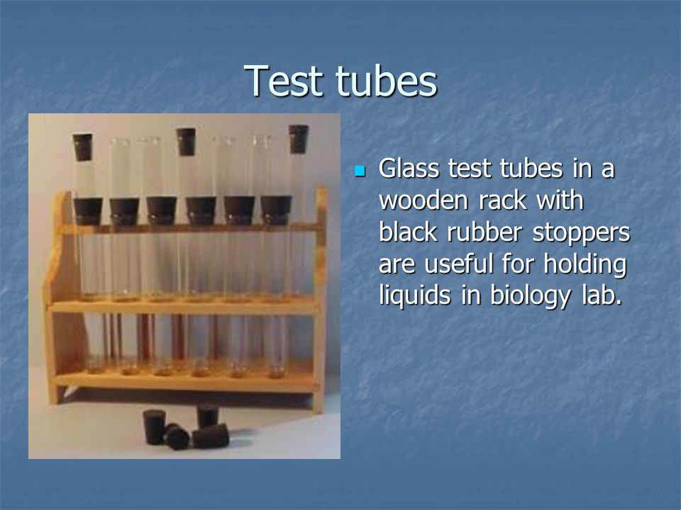 Test tubes Glass test tubes in a wooden rack with black rubber stoppers are useful for holding liquids in biology lab.
