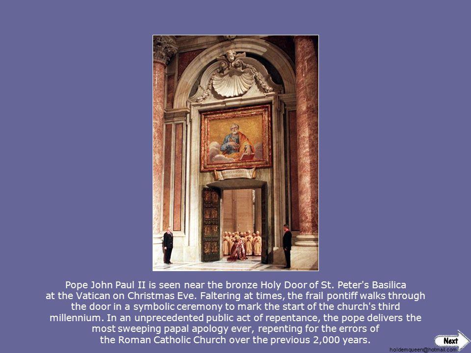 Pope John Paul II is seen near the bronze Holy Door of St