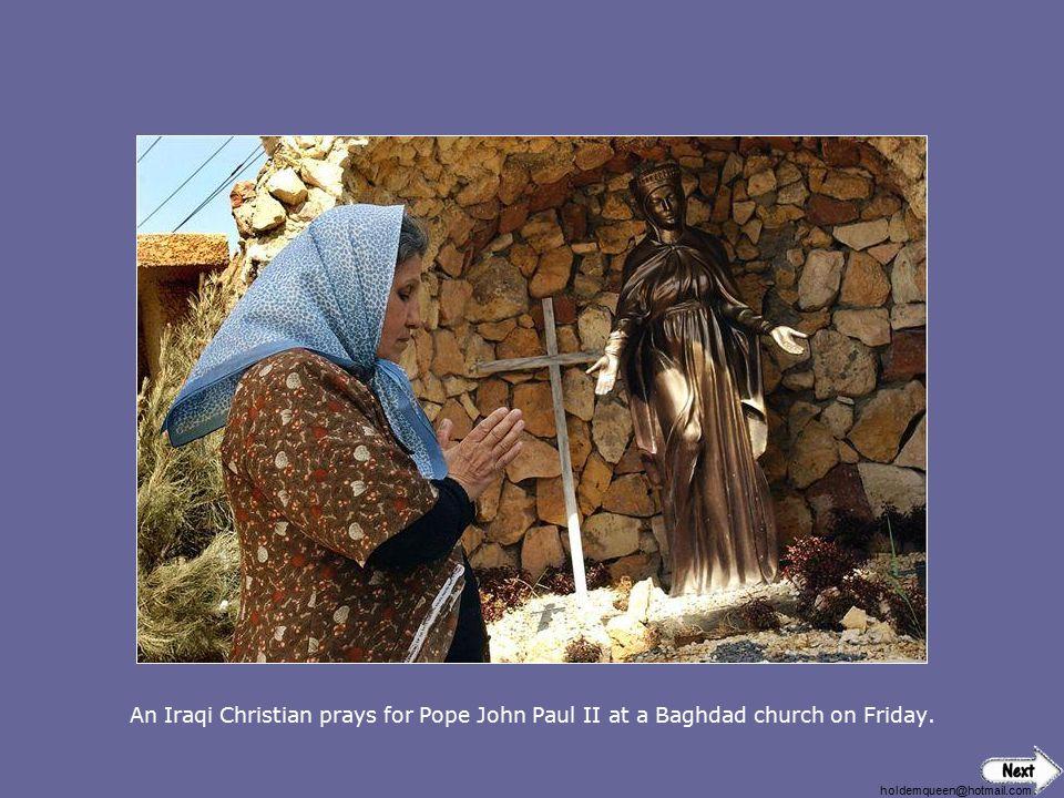 An Iraqi Christian prays for Pope John Paul II at a Baghdad church on Friday.
