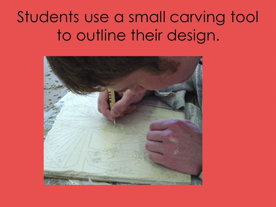 Students use a small carving tool to outline their design.