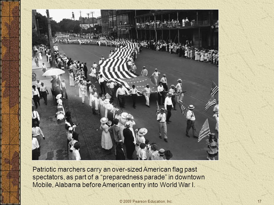 Patriotic marchers carry an over-sized American flag past spectators, as part of a preparedness parade in downtown Mobile, Alabama before American entry into World War I.