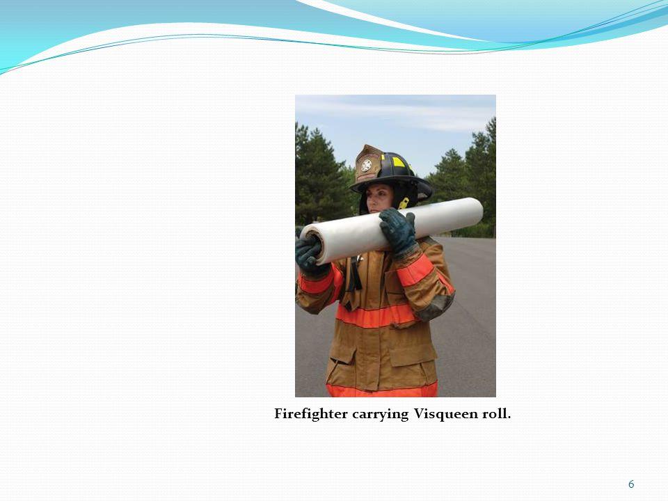 Firefighter carrying Visqueen roll.