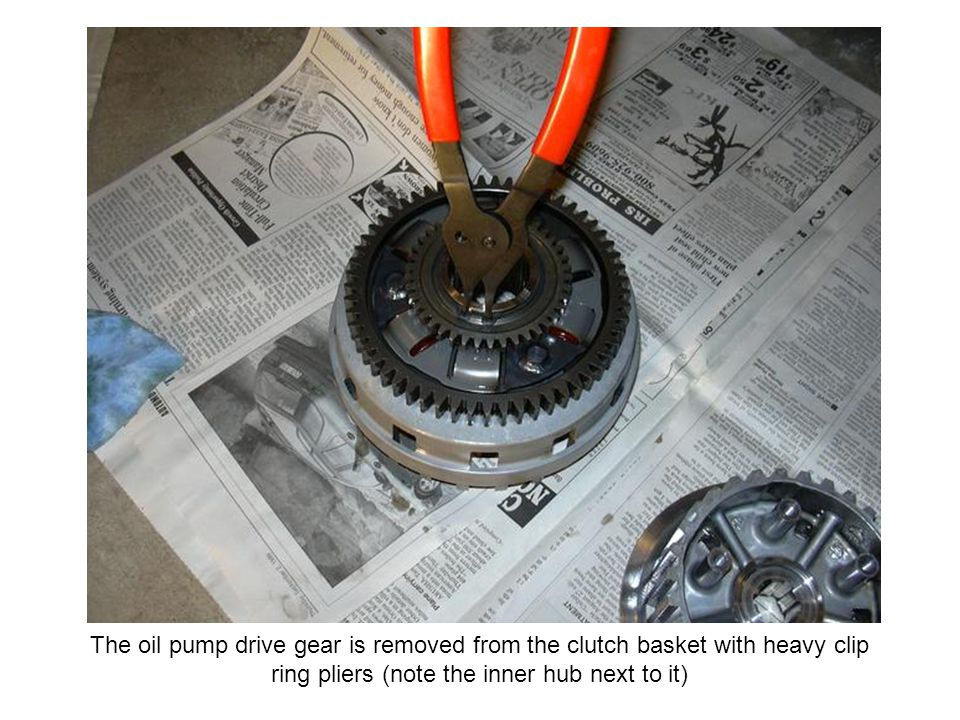 The oil pump drive gear is removed from the clutch basket with heavy clip ring pliers (note the inner hub next to it)