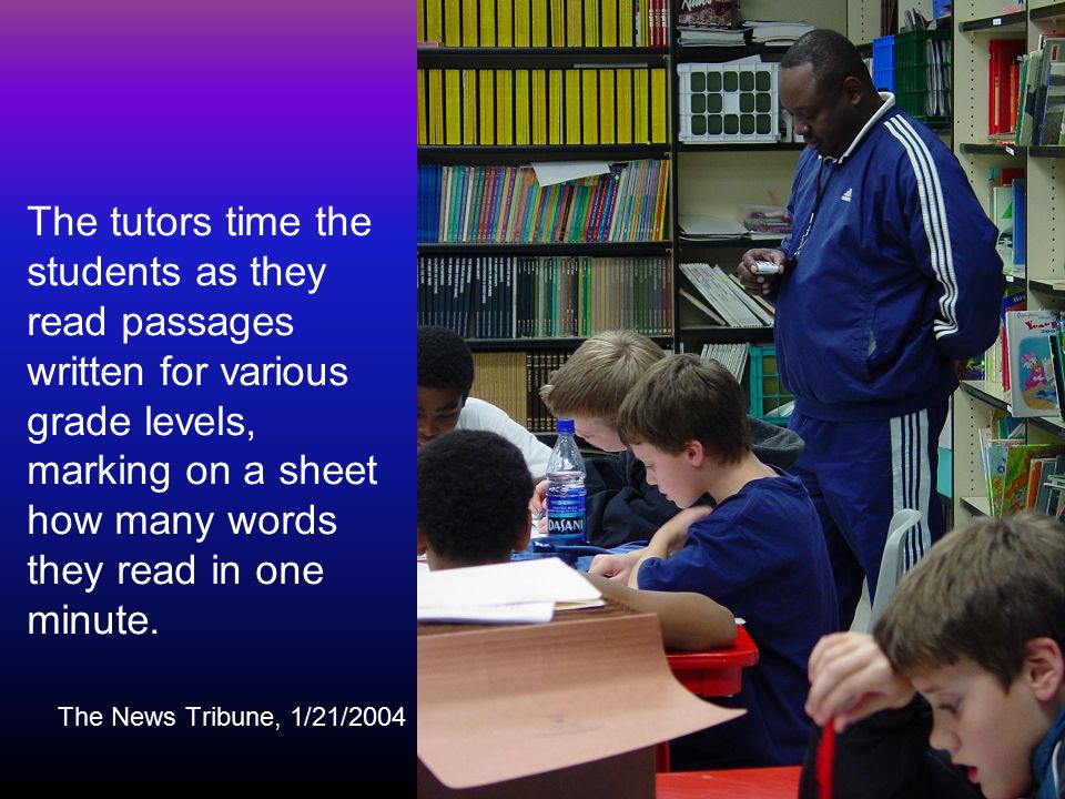The tutors time the students as they read passages written for various grade levels, marking on a sheet how many words they read in one minute.