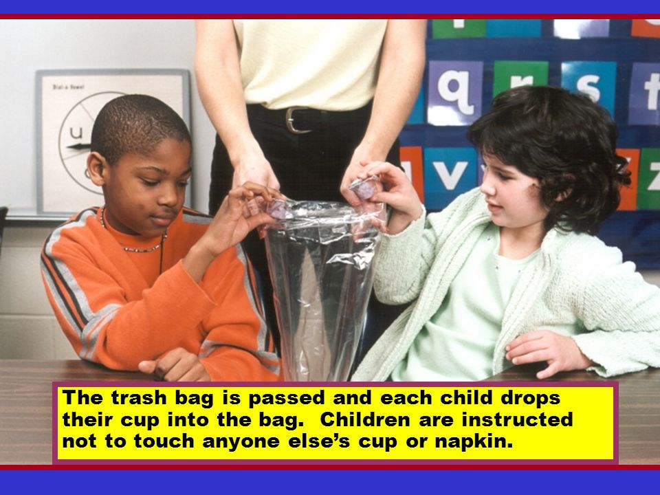 The trash bag is passed and each child drops their cup into the bag