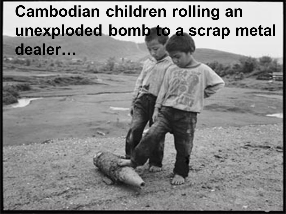 Cambodian children rolling an unexploded bomb to a scrap metal dealer…